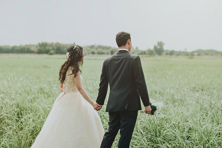 bride and groom running through field at wedding venue